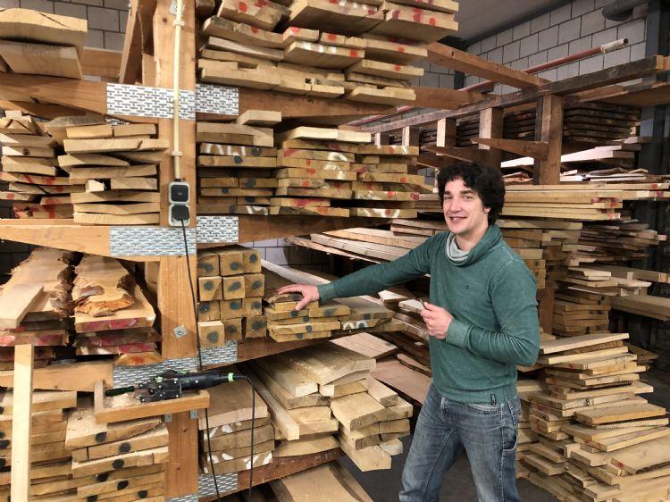 Jelmer van der Sluis bij de voorraad inmiddels gedroogd hout