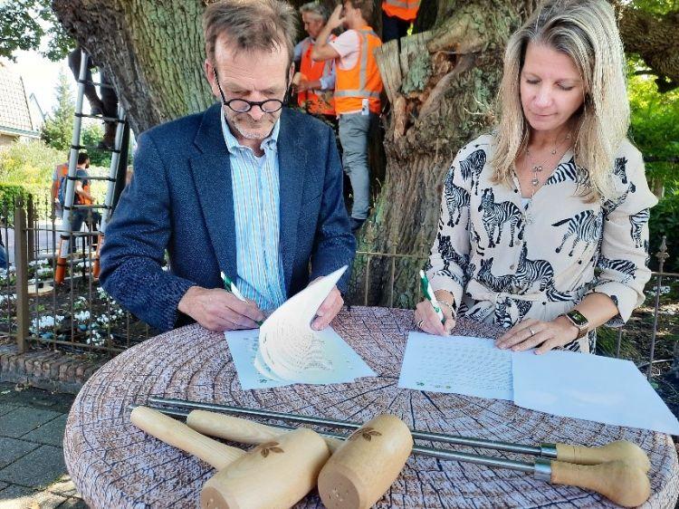 Mede-eigenaar Willem van Delft van Praktijk Centrum Bomen en directeur onderwijs Ruth van der Beek van Hogeschool Van Hall Larenstein ondertekenen onder De Kroezeboom te Ruurlo de samenwerkingsovereenkomst.